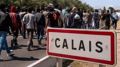Migrants walk on June 17, 2015 towards the ferry port of Calais, northern France. Around 3,000 migrants built makeshift shelters in the so-called 'New Jungle' before trying to go to England. AFP PHOTO / PHILIPPE HUGUEN        (Photo credit should read PHILIPPE HUGUEN/AFP/Getty Images)